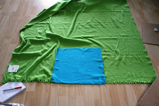 Cut out a square from one blanket and pin it at the bottom of the other blanket, centered.